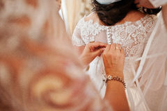 Bridesmaids helped dressed wedding dress for bride at room. Stock Images