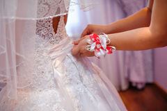 Bridesmaids helping the bride to wear a white wedding dress Stock Image