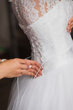 Bridesmaids helping to tie her wedding dress. tradition, the bride morning Royalty Free Stock Image