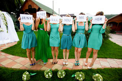 Bridesmaids hold a lettering 'Just wait till you see her' printe royalty free stock photos