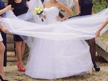 Bridesmaids Holding Bridal Dress Royalty Free Stock Image