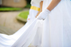 Bridesmaids holding bride's wedding dress Royalty Free Stock Photography