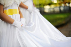 Bridesmaids holding bride's wedding dress Stock Image