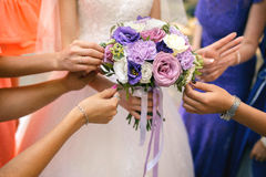Bridesmaids holding a wedding bouquet. Of white and lilac flowers Royalty Free Stock Photo
