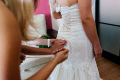 Bridesmaids lace bride dress. In the room Stock Photography
