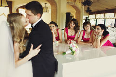Bridesmaids lean on a piano looking at a kissing wedding couple.  Stock Image