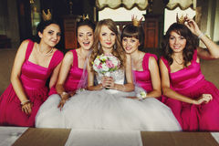 Bridesmaids in little crowns surrounded a bride on a sofa royalty free stock images