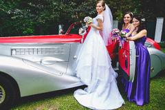 Bridesmaids open a door of vintage car for a bride Royalty Free Stock Image