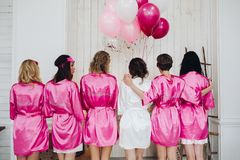 Bridesmaids in pink silk robes with the word `bridesmaid` on bac