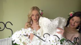 Bridesmaids are playing with a wedding dress. Happy women in dresses stock video