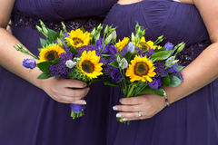 Bridesmaids in purple with sunflower bouquets Royalty Free Stock Photography