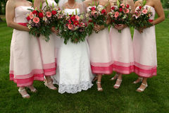 Bridesmaids Wedding. A Bride stands with her beautiful Bridesmaids as they all hold bouquets of flowers. The Bridesmaids are wearing pink dresses stock photos