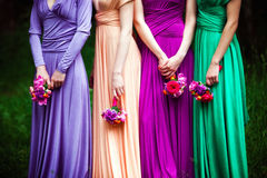 Bridesmaids on wedding. Bridesmaids in colorful dresses with bouquets of flowers stock photos