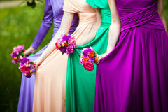 Bridesmaids on wedding. Bridesmaids in colorful dresses with bouquets of flowers royalty free stock image