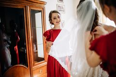 Bridesmaids help bride to get ready for a wedding royalty free stock image