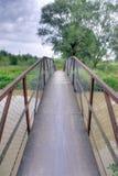 Bridge. A steel bridge leading over a river Royalty Free Stock Image