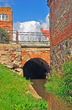 Bridge. Small stream flowing under a dark arch of the old brick bridge Stock Photo