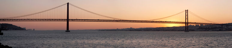 Bridge 25 de Abril on river Tagus at sunset, Lisbon. Panorama of bridge 25 de Abril on river Tagus at sunset, Lisbon, Portugal Royalty Free Stock Images