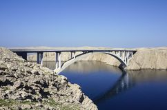 Bridge above the blue sea surface with reflection in the water, between the rocky land. White bridge above the blue sea surface with reflection in the water Stock Photo