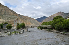 The bridge across affluent mountain Nepal river Stock Photo