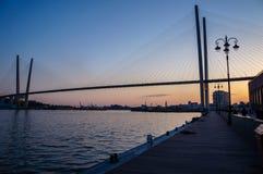 Bridge across the bay at sunset. And embankment in Vladivostok stock photo