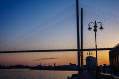 Bridge across the bay at sunset. And embankment in Vladivostok royalty free stock images