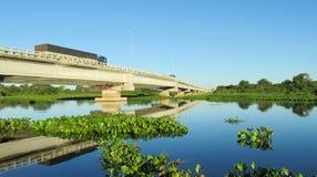 Bridge across blue water River Uruguay in Brazil. Bridge across blue water river, beautiful landscape. River Uruguay in Brazil. Tropical greenery plants floating stock photography