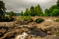 A bridge across falls of Dochart with tourists enjoying the view in a town of Killin. Central Scotland Stock Photos