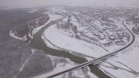 Bridge across a frozen river in winter in a small town near the forest stock video footage