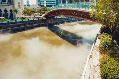 Bridge across Gombak river. Misty water. Kuala Lumpur cityscape. Connection concept. Travel to Malaysia. River embankment. City to. Ur. Tourism industry. Urban Stock Photos