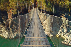 The bridge across green river. A suspension bridge across the green river in the mountains Royalty Free Stock Images