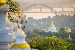 The bridge across Irrawadee river and the old pagodas in Sagaing Area. Royalty Free Stock Photography
