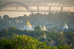The bridge across Irrawadee river and the old pagodas in Sagaing Area. Mandalay. Myanmar Royalty Free Stock Photo