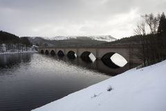 Bridge across lake in snow. Bridge across ladybower reservoir in the snow with mountains in the background peak district, uk Royalty Free Stock Image