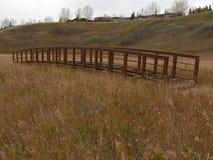 Bridge Across Meadow. Bridge spanning meadow in Fish Creek Park, Calgary, Alberta, Canada Stock Images