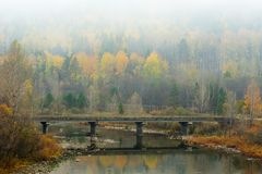 Bridge across mountain river in autumn Royalty Free Stock Image