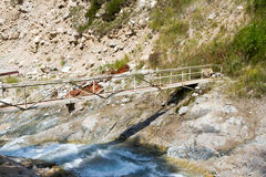 Bridge across mountain river. Bridge for hikers through a large mountain river Royalty Free Stock Photos