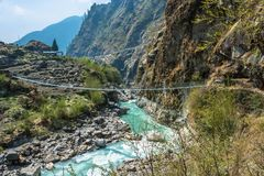 Bridge over the mountain river in Nepal. A bridge across the mountain river in a spring Sunny day in Nepal Stock Photos