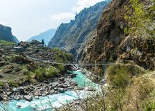 Bridge over the mountain river in Nepal. A bridge across the mountain river in a spring Sunny day in Nepal Royalty Free Stock Photo