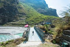 Bridge over the mountain river in Nepal. A bridge across the mountain river in a spring Sunny day in Nepal Stock Photography
