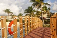 Bridge Across Pool in Warm Morning Light. A walking bridge across a tropical resort swimming pool in warm light Stock Photography