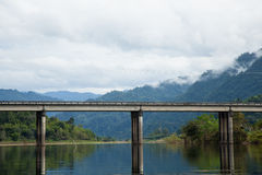 Bridge across the river. The mist covered mountains in the background Royalty Free Stock Photo