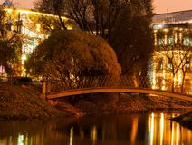 Old bridge over the river in a park on a background of modern buildings Royalty Free Stock Images