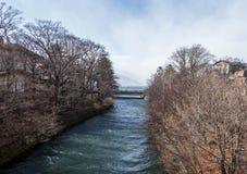 Bridge across river flow from lake, leads to Kegon falls Stock Photo