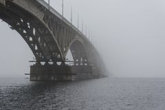 The bridge across the river in the fog. View from under the arch bridge to the river. Stock Photos