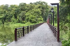 The bridge across the river with hanging lamps electrical poles. Royalty Free Stock Photography