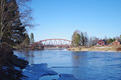 A bridge across a river. This small bridge across a river connects two parts of na village in Dalarna Stock Images