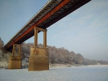 The bridge across the river. There is the reinforced concrete bridge for cars across the wide river on the winter Royalty Free Stock Image