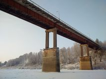 The bridge across the river. There is the reinforced concrete bridge for cars across the wide river on the winter Stock Photography