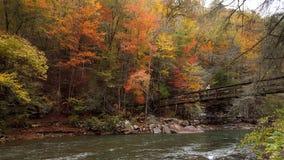 Bridge across stream in autumn royalty free stock photography